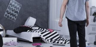 Mężczyzna patrzy na mieszkanie po kradzieży z włamaniem
