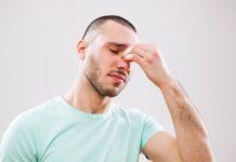 Płukanie zatok - młody mężczyzna trzymający się za bolący nos.